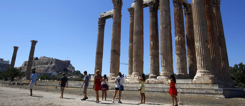 Turistas caminham no Templo de Zeus, a moradia do deus dos deuses, em Atenas Foto: YANNIS BEHRAKIS / REUTERS