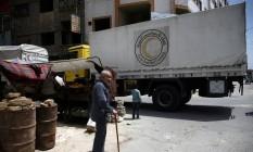 Um idoso anda perto de um comboio de ajuda do Crescente Vermelho transportando suprimentos médicos na sitiada cidade de Douma Foto: BASSAM KHABIEH / REUTERS