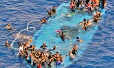 Imigrantes são vistos acenando por ajuda em barco naufragado em uma foto postada pela força naval da UE Foto: Reprodução Twitter