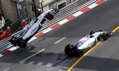 O Williams de Felipe Massa é içado e retirado da pista após acidente no treino livre para o GP de Mônaco, enquanto o outro carro da equipe, pilotado por Valtteri Bottas, passa pelo local Foto: VALERY HACHE / AFP