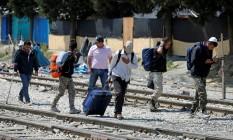 Imigrantes caminham por trilho de trem durante operação policial para esvaziar um campo na fronteira entre Grécia e Macedônia, perto de Idomeni Foto: MARKO DJURICA / REUTERS