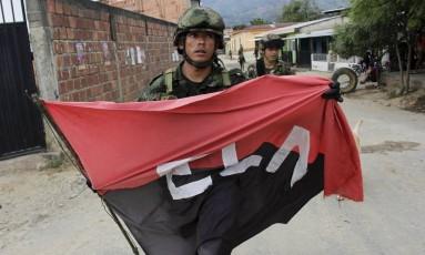 Soldado anda com bandeira do ELN apreendida em El Tarra, onde jornalistas sumiram Foto: DIARIO LA OPINION / ALFREDO ESTE / AFP