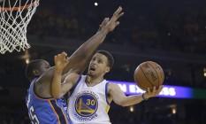 Curry vence o bloqueio de Kevin Durant para chegar à cesta na vitória do Golden State Warriors sobre o Oklahoma, pelo quinto jogo da série decisiva da Conferência Oeste Foto: Marcio Jose Sanchez / AP