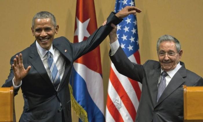 O presidente cubano Raúl Castro levanta o braço do presidente Barack Obama, após entrevista coletiva no Palácio da Revolução Foto: AP