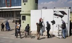 Pintores da organização ArtLords pintam mural de concreto em frente a guarita da Polícia Nacional em Cabul Foto: ADAM FERGUSON / NYT