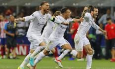 Sergio Ramos, Lucas Vazquez e Gareth Bale correm para comemorar assim que Cristiano Ronaldo, fora da foto, bate o último pênalti e decreta a vitória do Real Madrid por 5 a 3 na disputa de penais contra o Atlético de Madrid: campeão pela 11ª vez da Europa Foto: Stefan Wermuth / REUTERS