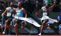 Justin Gatlin (à direita) ergue os braços e comemora a vitória na prova dos 100m da 4ª etapa da Liga Diamante, nos EUA, à frente de Tyson Gay e Asafa Powell Foto: Chris Pietsch / AP