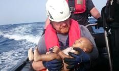 """O bebê nos braços do resgatista alemão: """"Parecia um boneco"""" Foto: HANDOUT / REUTERS"""