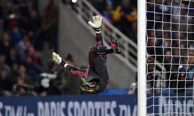Goleiro camaronês Fabrice Ondoa voa, mas não alcança a falta cobrada pelo francês Dimitri Payet Foto: FRANCK FIFE / AFP