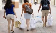 Consumidores caminham com suas compras em shopping no Texas, nos Estados Unidos Foto: Laura Buckman / Bloomberg