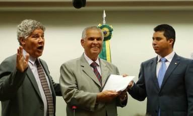 Observado pelo deputado Chico Alencar (PSOL-RJ), José Carlos Araújo (PR-BA), presidente da Comissão de Ética da Câmara, recebe de Marcos Rogério (DEM-RO), relator do conselho, voto sobre o caso Foto: Michel Filho / O Globo