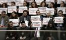 No plenário do Parlamento, um grupo de pessoas segura cartazes em que se lê