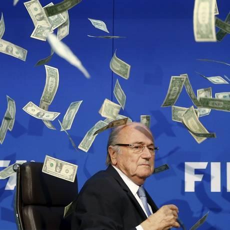 Joseph Blatter leva banho de dinheiro falso em entrevista coletiva na Fifa, em 2015 Foto: ARND WIEGMANN / REUTERS