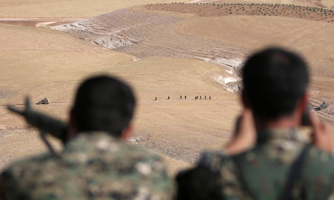 Milicianos das Forças Democráticas da Síria observam o aavanço de colegas na zona rural de Manbij, uma das quaatro frentes de luta que o Estado Islâmico enfrenta atualmente Foto: REUTERS/RODI SAID
