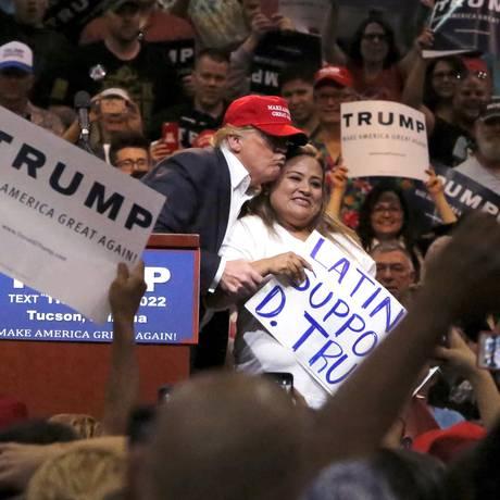 Abraço. Trump abraça uma eleitora de origem latina em Tucson, Arizona: parte da população imigrante ignora os ataques e promete apoio ao republicano Foto: © Sam Mircovich / Reuters / Reuters/19-3-2016
