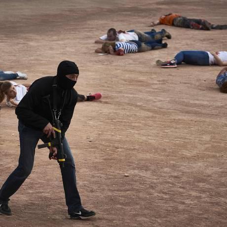 Homem, com arma em mãos, simula um ataque suicida durante treinamento antiterrorismo em Lyon, na França: cuidados na Euro-2016 Foto: JEAN-PHILIPPE KSIAZEK / AFP