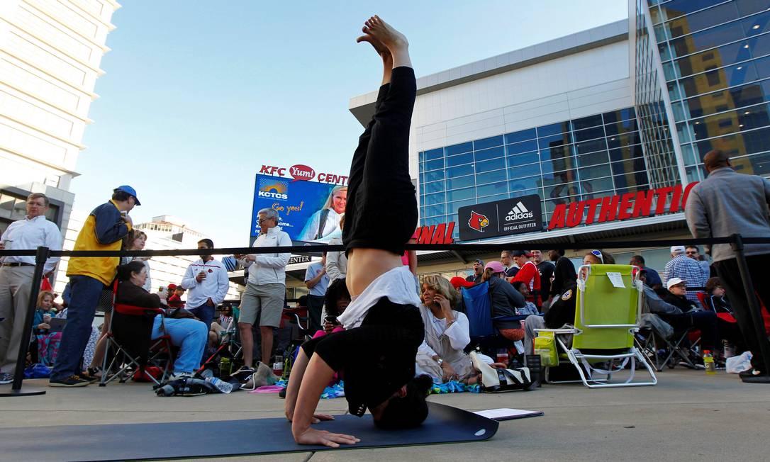 Enquanto espera na fila por ingresso para o funeral de Muhammad Ali, mulher pratica yoga para relaxar JOHN SOMMERS II / REUTERS