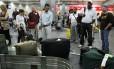 Passageiros aguardam suas bagagens na esteira do Aeroporto do Galeão