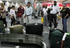 Passageiros aguardam suas bagagens na esteira do Aeroporto do Galeão Foto: Ana Branco / Agência O Globo/Arquivo