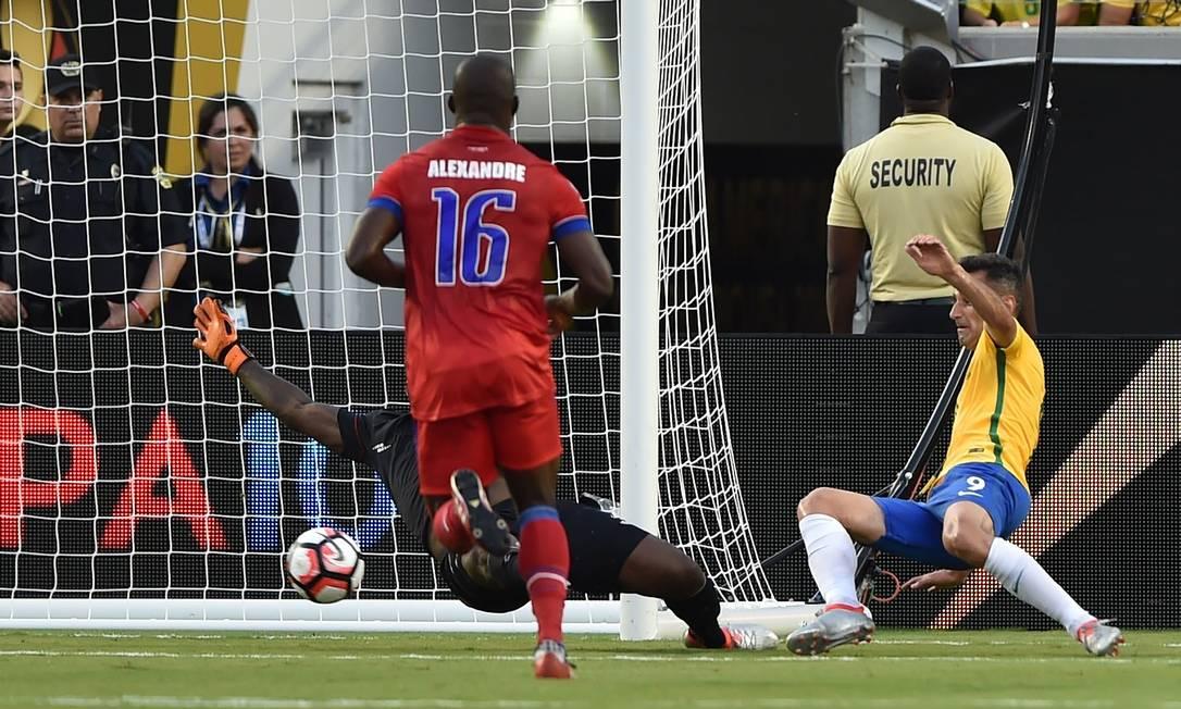 Jonas toca a bola na saída do goleiro Placide na partida entre Brasil e Haiti HECTOR RETAMAL / AFP