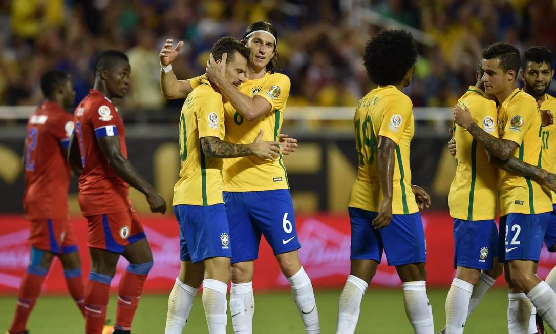 Lucas Lima é abraçado por Filipe Luis ao fazer o quinto gol do time de Dunga HECTOR RETAMAL / AFP