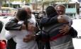Familiares de vítimas do acidente com ônibus em São Paulo se abraçam na frente do IML do Guarujá