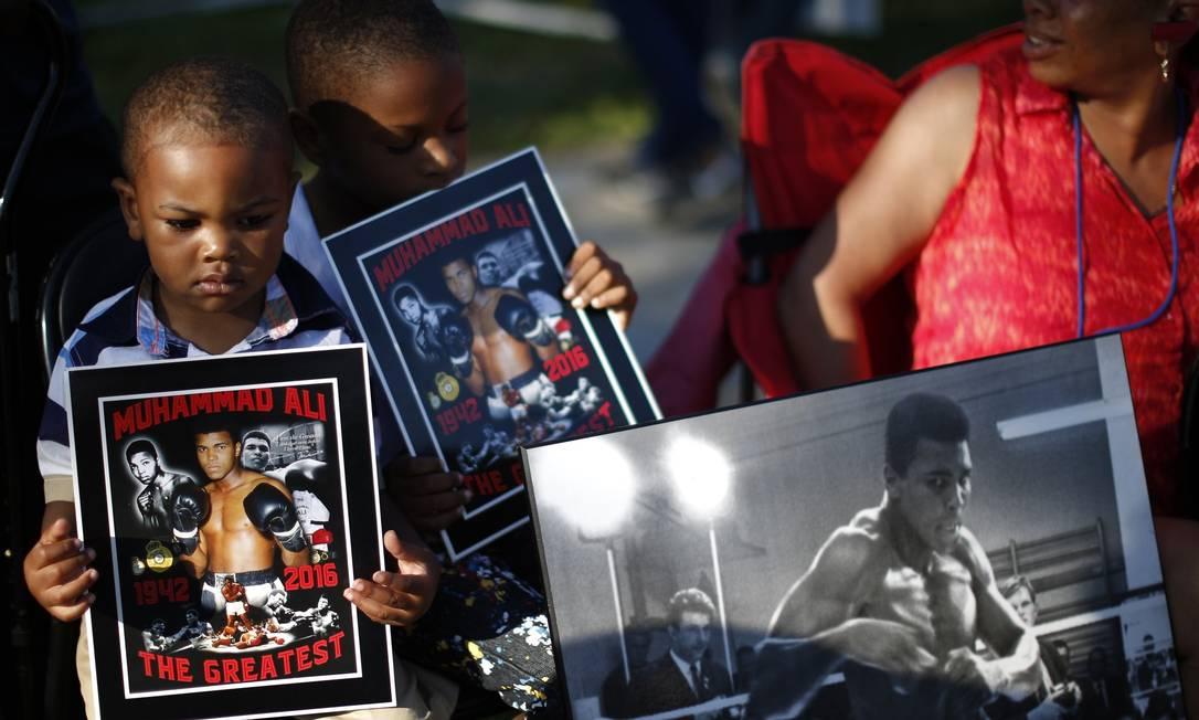 Os garotinhos seguram cartazas homenageando Muhammad Ali, o maior de todos, como ele gostava de dizer sobre si mesmo LUCY NICHOLSON / REUTERS
