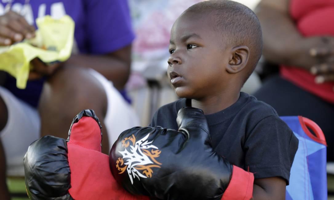 Tymetrius Steward, de 3 anos, com luvas de boxe, participa das últimas homenagens a Muhammad Ali Michael Conroy / AP