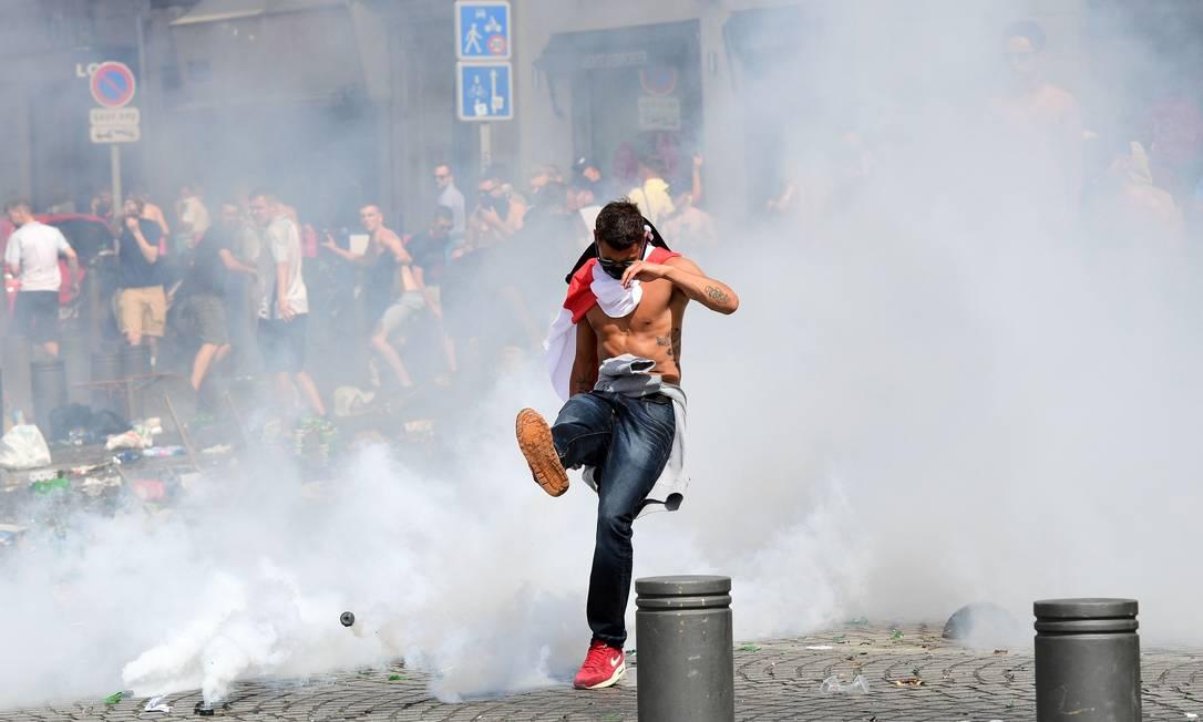 Torcedor inglês chuta uma bomba de gás lacrimogênio lançada pela polícia durante o tumulto entre hooligans LEON NEAL / AFP