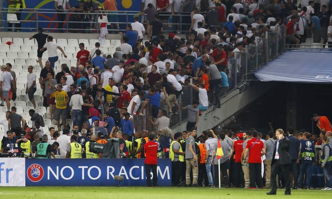 Torcedores tentam pular a grave enquanto durante a confusão no estádio Jason Cairnduff / REUTERS