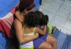 Mãe de menina morta no Morro da Barão fica abraçada às filhas: medo de perder mais alguém para o tráfico Foto: Vera Araújo / Agência O Globo