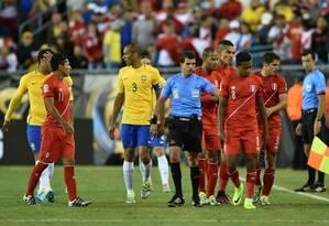 Andres Cunha é cercado por jogadores de Brasil e Peru após o gol de Ruidiaz: demora para validar gol irregular Foto: HECTOR RETAMAL / AFP