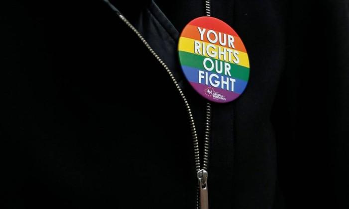 """Mulher usa broche com a frase """"seus direitos, nossa luta"""" em vígilia em memória dos mortos no ataque de Orlando Foto: FRANCOIS LENOIR / REUTERS"""