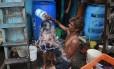 Homem dá banho em seu filho em Mumbai, na Índia: diferença de temperatura do mês em relação a períodos anteriores diminuiu