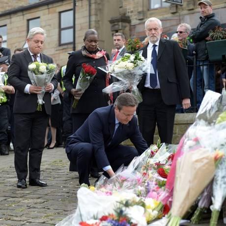 Unidade. Cameron (agachado) deixa flores em memória à deputada Jo Cox, observado pelo líder trabalhista Jeremy Corbyn (à direita): união entre adversários políticos Foto: OLI SCARFF/AFP