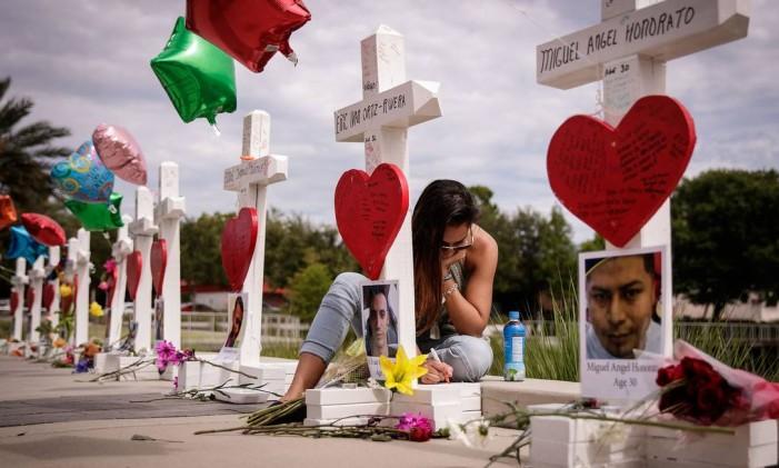 Mulher escreve mensagem ao lado de memorial a vítimas de ataque a boate em Orlando Foto: Drew Angerer / AFP