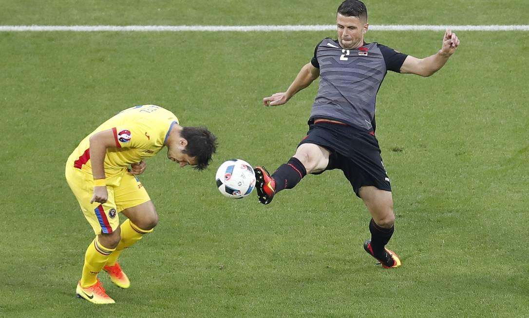 Alexandru Matel, da Romênia, abaixa a cabeça para tentar roubar a bola de Andi Lila, da seleção albanesa Michael Sohn / AP
