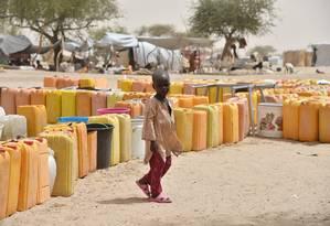 Uma criança deslocada caminha ao lado de caixas de água durante distribuição pelos agentes da ONU no campo de refugiados de Kidjendi, em torno de Diffa, sudeste do Níger Foto: ISSOUF SANOGO / AFP