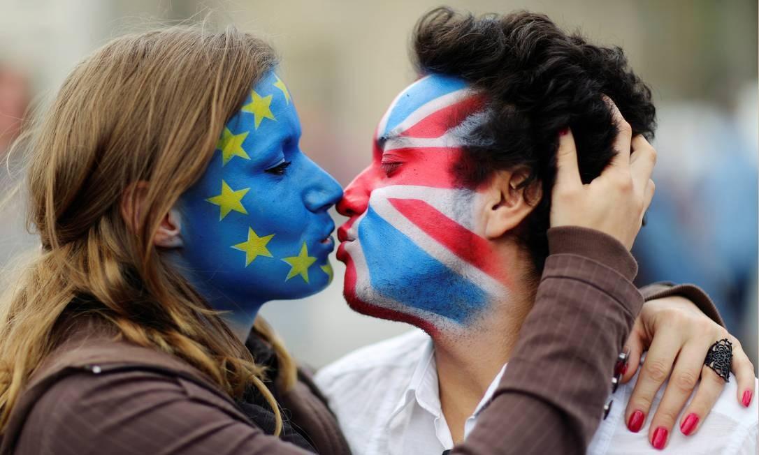Manifestantes se beijam na frente do Portão de Brandemburgo, na Alemanha Foto: Reuters/Hannibal Hanschke