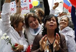 Emoção. Colombianas comemoram no Centro de Bogotá o cessar-fogo entre o governo e as Farc: a assinatura do acordo foi acompanhada por um telão Foto: Fernando Vergara / AP