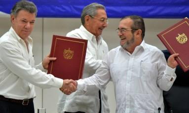 Sorrisos. Juan Manuel Santos (à esquerda) e Timochenko apertam as mãos após anunciar cessar-fogo definitivo: acordo final será assinado na Colômbia Foto: ADALBERTO ROQUE/AFP
