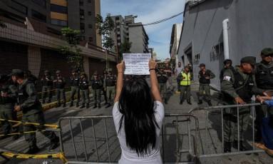 Jovem mostra placa para memebros das forças de segurança durante protesto em frente à sede do Conselho Nacional Eleitoral, em Caracas Foto: JUAN BARRETO / AFP