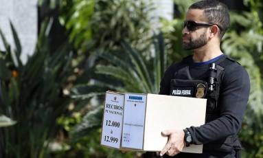 Agente da PF carrega documentos retirados da sede nacional do PT em São Paulo Foto: Edilson Dantas / Agência O Globo / 23-6-2016