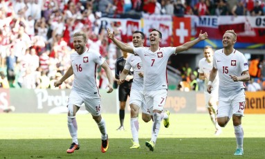 Jogadores da Polônia correm para o abraço após a vitória na disputa por pênaltis Foto: Kai Pfaffenbach / REUTERS