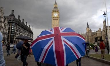 Pedestre se abriga da chuva com uma sombrinha temática com a bandeira do Reino Unido perto do Parlamento britânico, no centro de Londres Foto: JUSTIN TALLIS / AFP