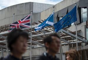 Bandeiras do Reino Unido, da Escócia e da UE tremulam em frente ao edifício do Parlamento escocês em Edimburgo, na Escócia Foto: OLI SCARFF / AFP