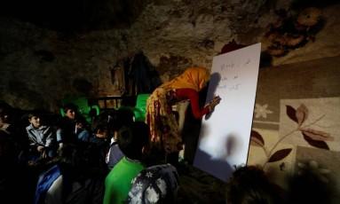 Professora dá aula para crianças sírias em caverna que tem 120 alunos Foto: KHALIL ASHAWI / REUTERS
