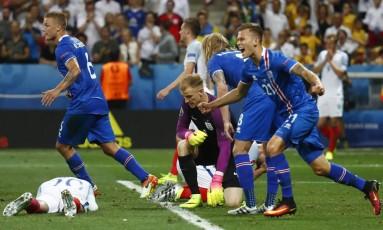 A desolação inglesa contrata com a alegria dos jogadores da Islândia ao fim do jogo Foto: Kai Pfaffenbach / REUTERS