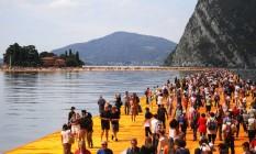 Pessoas caminham sobre a instalação de Christo, no Lago Iseo, norte da Itália Foto: MARCO BERTORELLO / AFP
