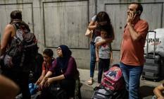 Passageiros aguardam fora do aeroporto de Ataturk, em Istambul Foto: OZAN KOSE / AFP